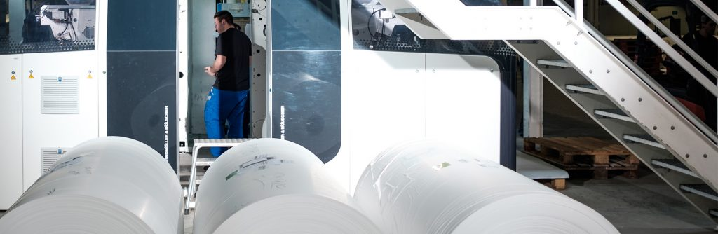 In the factory: Three large rolls of film by a machine.